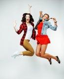 Morenita bonita dos y amigos de adolescente rubios que saltan la sonrisa feliz en el fondo blanco, concepto de la gente de la for Fotografía de archivo