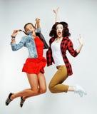 Morenita bonita dos y amigos de adolescente rubios que saltan la sonrisa feliz en el fondo blanco, concepto de la gente de la for Imagen de archivo