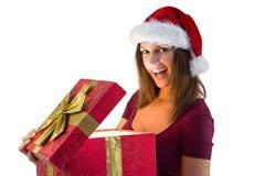 Morenita bonita en el sombrero de santa que abre un regalo que sonríe en la cámara Imágenes de archivo libres de regalías