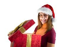 Morenita bonita en el sombrero de santa que abre un regalo que sonríe en la cámara Fotografía de archivo libre de regalías