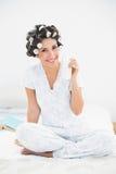 Morenita bonita en los rodillos del pelo que sostienen el vidrio de leche que sonríe en Foto de archivo