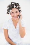 Morenita bonita en rodillos del pelo en el teléfono en cama Imágenes de archivo libres de regalías
