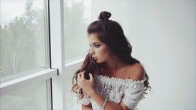 Morenita bonita joven de la mujer que plantea sentarse cerca de la ventana almacen de metraje de vídeo