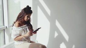 Morenita bonita joven de la mujer usando su tableta en el fondo blanco cerca de la ventana almacen de video