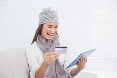 Morenita bonita sonriente con el sombrero del invierno en la compra en línea Foto de archivo