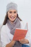 Morenita bonita sonriente con el sombrero del invierno en la escritura en el cuaderno Imagenes de archivo