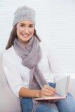 Morenita bonita sonriente con el sombrero del invierno en la escritura en su cuaderno Imágenes de archivo libres de regalías