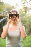 Morenita bonita sonriente que mira a través de los prismáticos Imagen de archivo