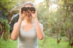 Morenita bonita sonriente que mira a través de los prismáticos Imagenes de archivo