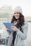 Morenita bonita sonriente que sostiene su PC de la tableta Fotografía de archivo