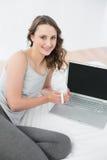 Morenita casual con la taza de café y el ordenador portátil en cama Fotografía de archivo