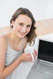 Morenita casual con la taza de café y el ordenador portátil en cama Imágenes de archivo libres de regalías