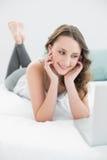 Morenita casual sonriente con el ordenador portátil en cama Imagenes de archivo