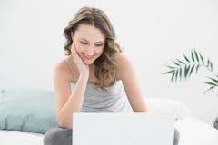 Morenita casual sonriente que mira el ordenador portátil en cama Imágenes de archivo libres de regalías