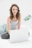 Morenita casual sonriente usando el ordenador portátil en cama Imagenes de archivo
