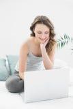 Morenita casual sonriente usando el ordenador portátil en cama Foto de archivo