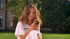 Morenita caucásica joven que se sienta en parque en hierba, usando un smartphone, movimiento en sentido vertical, mecanografiando almacen de metraje de vídeo