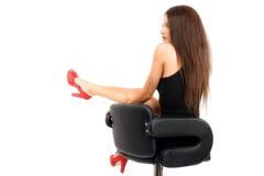 Morenita caucásica magnífica joven en vestido negro en la silla Foto de archivo