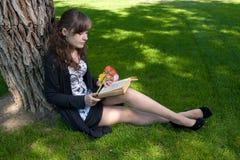 Morenita con el libro de lectura de las flores en hierba Imagen de archivo