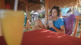 Morenita con el pelo corto que se sienta en un banco en un café en la isla Muy la enfocan, y mira en la distancia almacen de metraje de vídeo