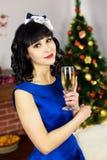 Morenita con un vidrio de champán para la Navidad fotos de archivo