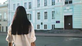 Morenita de la elegancia con el pelo largo que se mueve al edificio azul en la cámara lenta almacen de metraje de vídeo