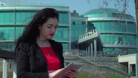 Morenita de la elegancia con los labios rojos usando la tableta digital cerca del centro de la oficina metrajes