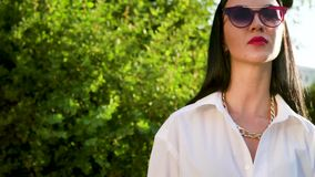Morenita de la elegancia en la camisa blanca y con la mano tattoed que presenta para la cámara almacen de video