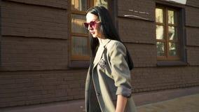 Morenita de la elegancia en la capa y las gafas de sol que se mueven en la cámara lenta almacen de video