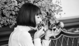 Morenita de la muchacha con la barra de labios que mira en espejo para comprobar su aspecto del maquillaje Concepto de ni?a de lo fotos de archivo libres de regalías