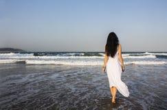 Morenita de la muchacha en el vestido blanco que entra en el Océano Índico fotos de archivo libres de regalías