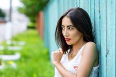 Morenita de la muchacha en un parque en la blusa blanca de reclinación del verano en el fondo de la cerca de madera, forma de vid Imagen de archivo libre de regalías
