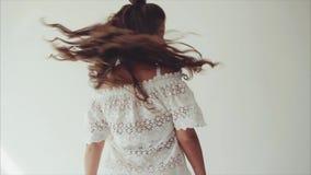 Morenita de la mujer joven que presenta en estudio en el fondo blanco y que camina a la cámara metrajes
