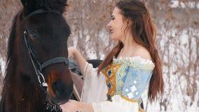 Morenita de pelo largo atractiva en un vestido y su caballo en el invierno, besándose y sonriendo almacen de metraje de vídeo
