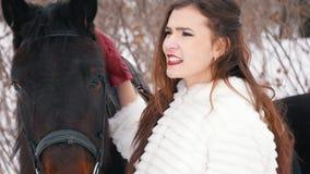 Morenita de pelo largo atractiva en un vestido y su caballo en invierno metrajes