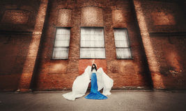 Morenita de pelo largo en el ángel azul-blanco del vestido Foto de archivo