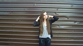 Morenita de pelo largo joven que presenta contra la cerca marrón del metal, imagen entonada Fotos de archivo libres de regalías