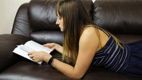 Morenita de pelo largo que lee cuidadosamente un libro almacen de metraje de vídeo