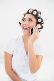 Morenita de risa en rodillos del pelo en el teléfono en cama Fotos de archivo libres de regalías