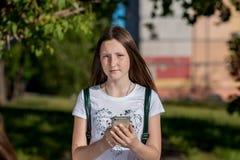 Morenita del adolescente en verano un parque al aire libre Lleva a cabo las manos del teléfono Él mira de cerca el marco Llamada Imagenes de archivo