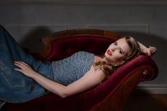 morenita del estilo de los años 40 en el sofá de desfallecimiento foto de archivo
