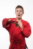 Morenita del muchacho del deportista en un kimono rojo Fotos de archivo