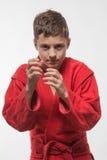 Morenita del muchacho del deportista en un kimono rojo Fotos de archivo libres de regalías