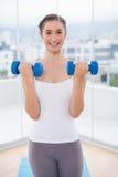 Morenita deportiva alegre que ejercita con pesas de gimnasia Imagen de archivo libre de regalías