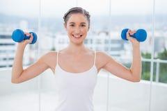 Morenita deportiva feliz que ejercita con pesas de gimnasia Foto de archivo libre de regalías