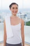 Morenita deportiva sonriente con la toalla blanca en hombro Imagenes de archivo