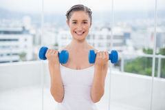 Morenita deportiva sonriente que ejercita con pesas de gimnasia Fotografía de archivo libre de regalías