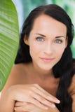 Morenita desnuda hermosa que sonríe en la cámara con la hoja verde Imágenes de archivo libres de regalías
