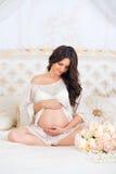 Morenita embarazada hermosa que se sienta en una cama en la posición de loto Imágenes de archivo libres de regalías