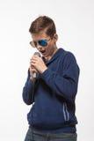 Morenita emocional del muchacho del adolescente en gafas de sol con un micrófono Fotos de archivo